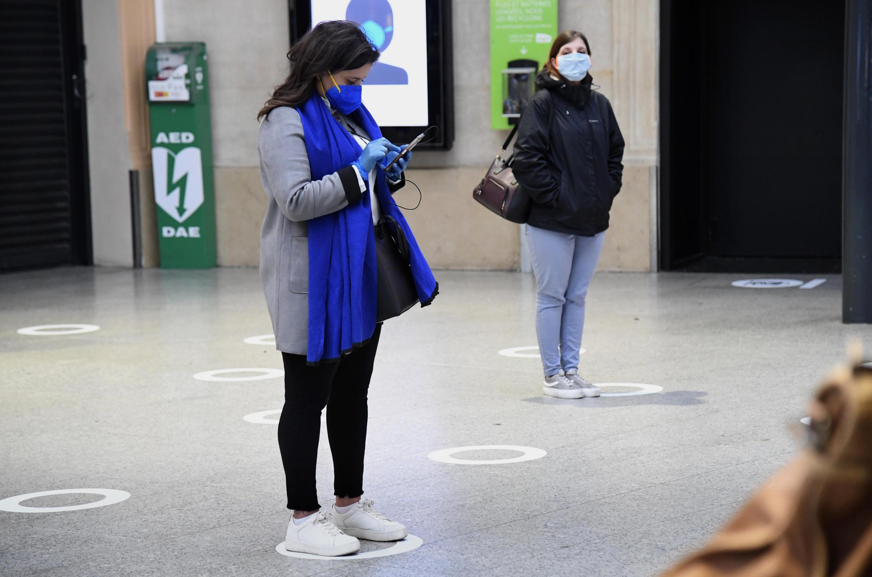 Los pasajeros esperan su turno marcado con adhesivos para mantener la distancia de seguridad en la estación de tren de Saint-Laraze en París, Francia, el 11 de mayo de 2020.