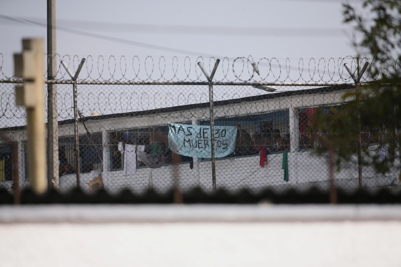 """Dans la prison de La Modelo en Colombie, les détenus brandissent un drap où il est écrit """"plus de 30 morts"""". Ils demandent au gouvernement de prendre des mesures contre l'épidémie de Coronavirus, le 22 mars 2020, à Bogota."""