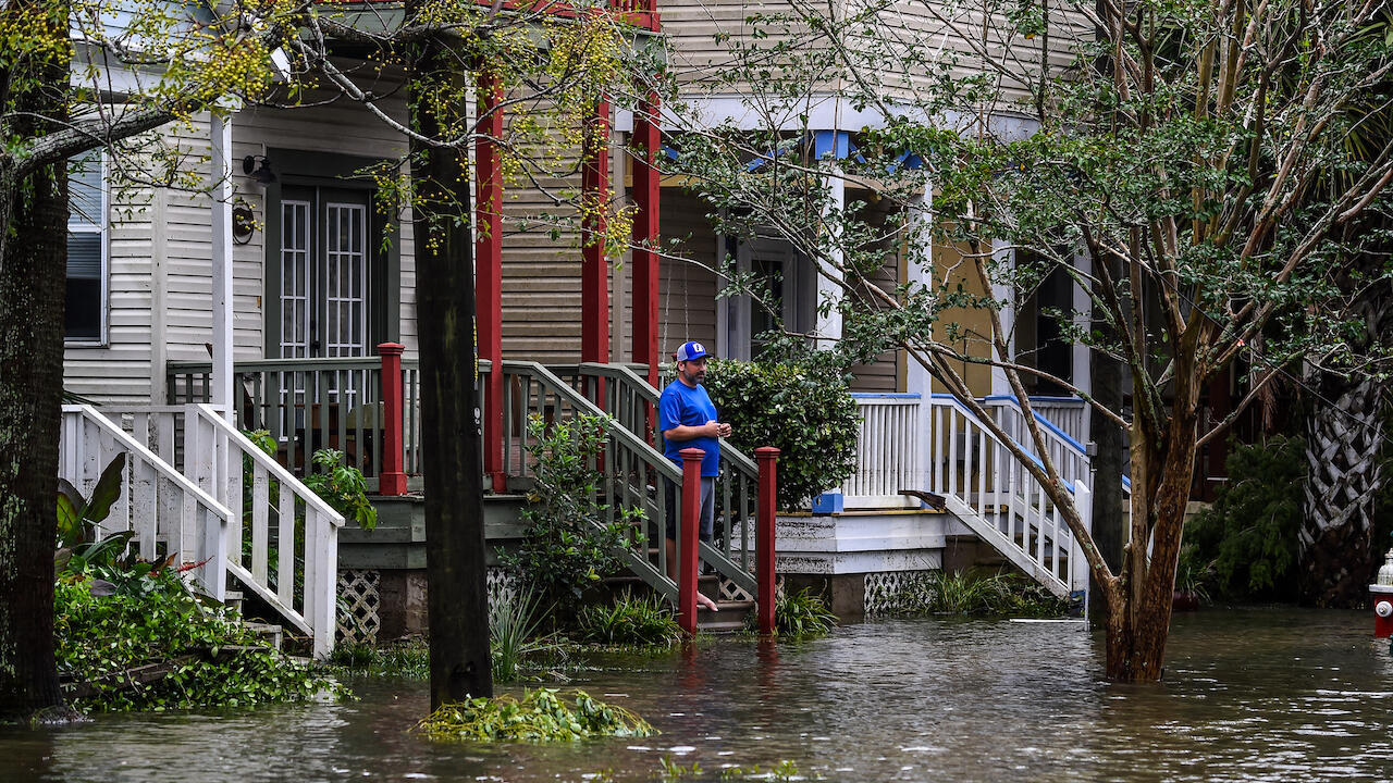 A man, standing outside of his home,watches a street flooded by Hurricane Sally in Pensacola, Florida, on September 16, 2020.