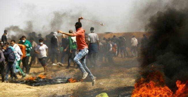 متظاهرون فلسطينيون على السياج الحدودي شرق قطاع غزة في 06 نيسان/أبريل 2018