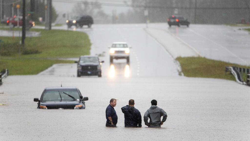 Dos transeúntes ayudan a un automovilista varado después de que las lluvias provocadas por el huracán Florence inundaran su carro en la ruta 17 cerca de Holly Ridge, Carolina del Norte, EE. UU., El 15 de septiembre de 2018.