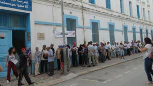 ناخبون يصطفون في طابور أمام مركز انتخاب بشارع مرسيليا بالعاصمة التونسية قبيل فتح باب الاقتراع. 15 سبتمبر/أيلول 2019.