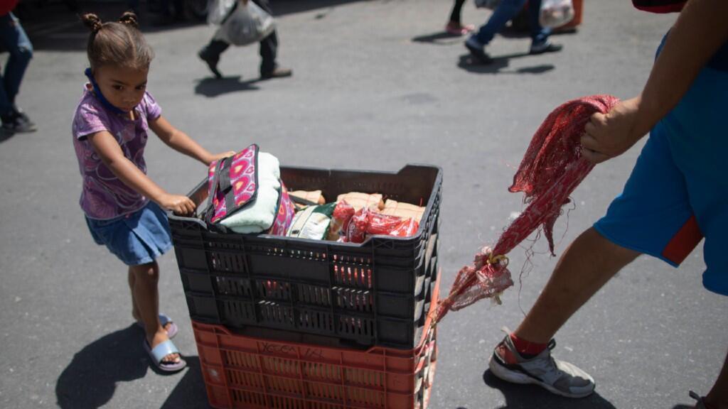 Una niña ayuda a su madre a transportar un mercado de productos básicos en la ciudad de Caracas, Venezuela. 8 de julio de 2020.