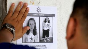 Un policía pega un afiche de Nora Quoirin, la menor que desapareció en Malasia el 4 de agosto.