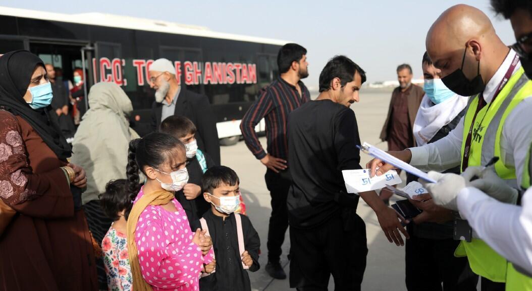 Archivo-Pasajeros con destino a Qatar reciben sus boletos antes de abordar un vuelo en el Aeropuerto Internacional Hamid Karzai, en Kabul, Afganistán, el 10 de septiembre de 2021.