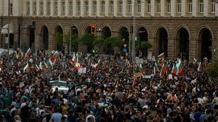 Protestors shout slogans and wave Bulgarian national flags during an anti-government protest in Sofia, on July 13, 2020