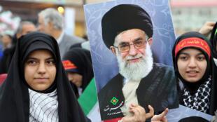 De jeunes Iraniennes célèbrent le 36e anniversaire de la révolution islamique à Téhéran et brandissent des portraits d'Ali Khamenei.