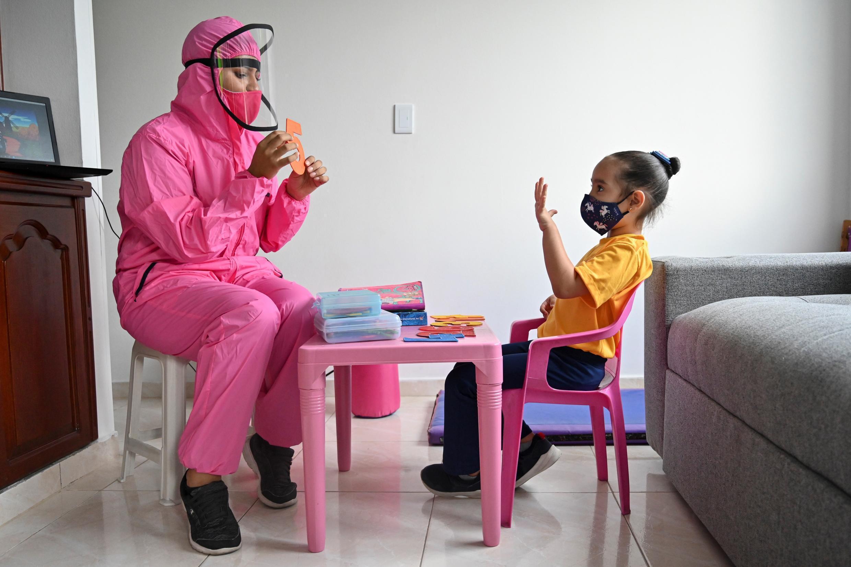 Una maestra, que usa un traje de bioseguridad como medida preventiva contra la propagación del nuevo coronavirus, da clase a una niña en su casa en Cali, Colombia, el 4 de agosto de 2020.