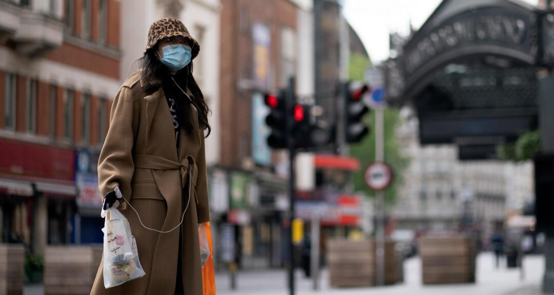 Una ciudadana pasea por las calles vacías con tiendas cerradas en el centro de Londres, Reino Unido, el 12 de mayo de 2020, un día antes del inicio de la desescalada por el brote de coronavirus en el país.