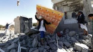 يمنيون أمام منازلهم المدمرة بصنعاء جراء غارة للتحالف العربي بقيادة السعودية