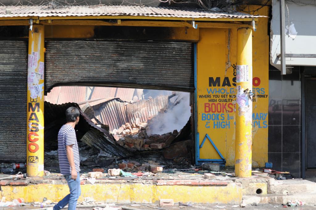 Un hombre pasa junto a una tienda después de los disturbios y saqueos en el municipio de Alexandra, en Johannesburgo, Sudáfrica. 3 de septiembre de 2019.