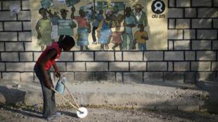Un niño con un juguete casero junto a un letrero de Oxfam en Corail, un campamento para personas desplazadas del terremoto de 2010, en las afueras de Puerto Príncipe, Haití, el 17 de febrero de 2018.