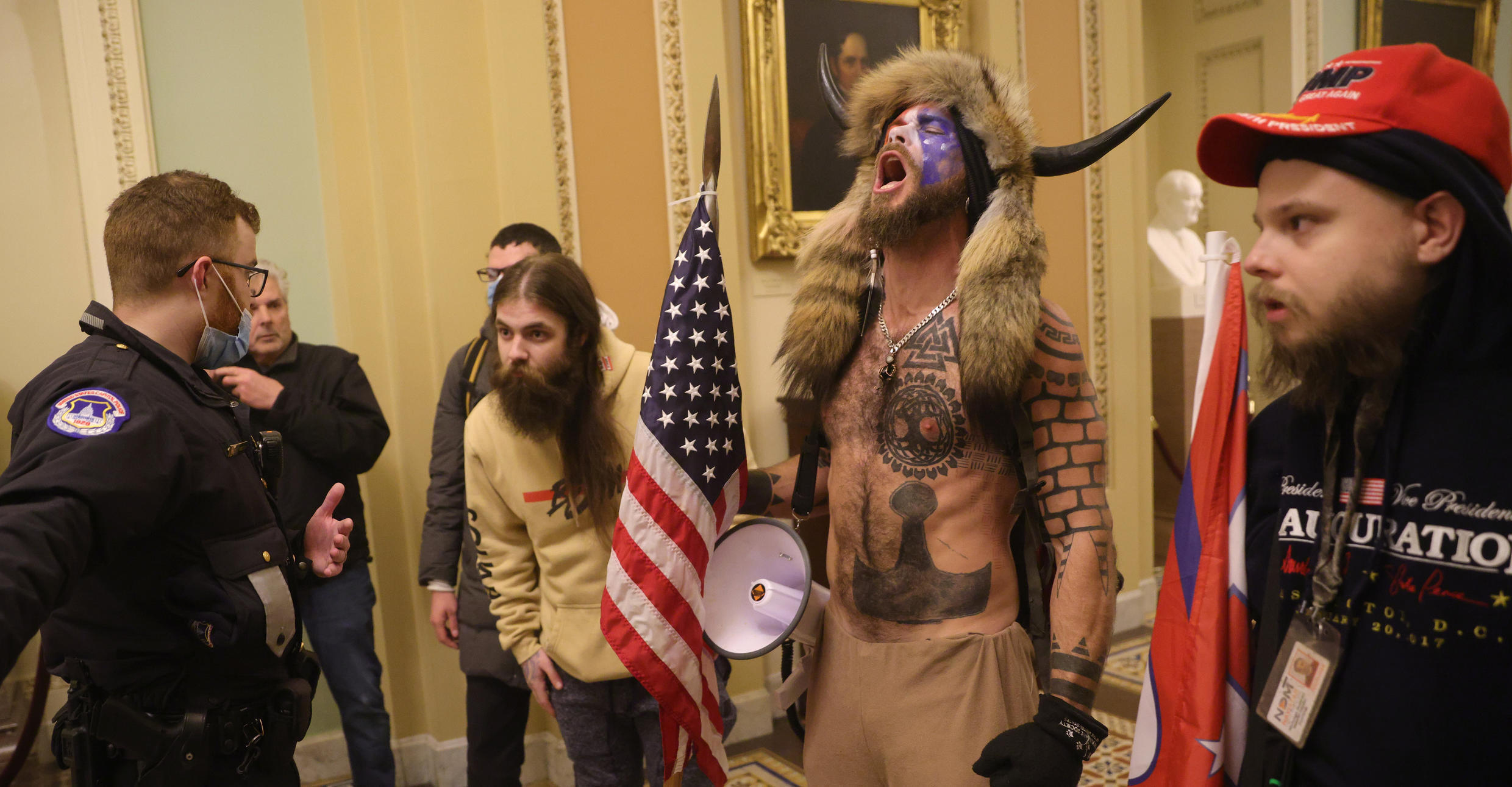 Jake Angeli, second from right, is a prominent supporter of the far-right QAnon conspiracy theory.