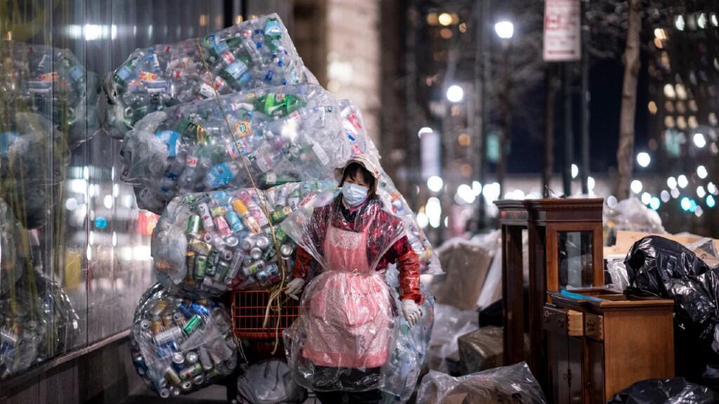 Una mujer transporta residuos de plástico en Nueva York, Estados Unidos, en una imagen del 16 de marzo de 2020, protegida ella misma por una capa de plástico desechable a causa de la pandemia de coronavirus.