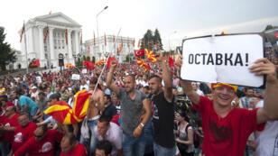 """Un homme tient une pancarte sur laquelle il est écrit """"démission"""", lors de la manifestation anti-gouvernementale, le 17 mai 2015, à Skopje."""