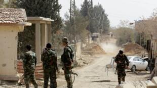 قوات النظام السوري أمام مدخل حرستا في الغوطة الشرقية في 22 آذار/مارس