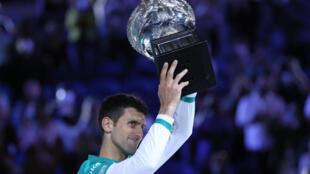 الصربي نوفاك ديوكوفيتش حاملاً كأس نورمان بروكس بعد فوزه بنهائي بطولة أستراليا المفتوحة على الروسي دانيل ميدفيديف في 21 شباط/فبراير 2021