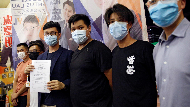 El activista político Ventus Lau Wing-hong (3rd-L) habla a los medios después de que fue descalificado para postularse a las elecciones a la legislatura en Hong Kong, China el 30 de julio de 2020.