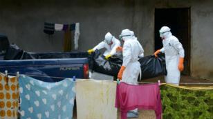 Les services sanitaires évacuent le corps d'une victime d'Ebola, dans la banlieue de Monrovia, le 4 septembre 2014