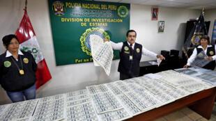 Agentes de la policía muestran dólares falsos después de que una pandilla dedicada a su producción fuera desmantelada en Lima el 10 de mayo de 2014.