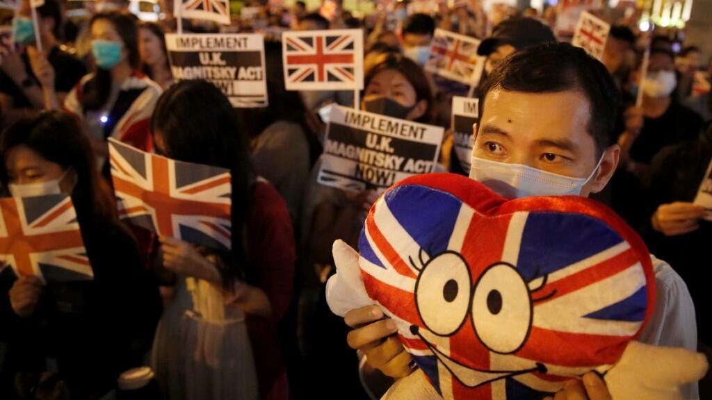 Manifestantes antigubernamentales sostienen pancartas y banderas británicas mientras protestan frente al consulado del Reino Unido en Hong Kong, China, el 23 de octubre de 2019.