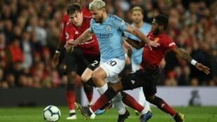 L'attaquant argentin de Manchester City Sergio Aguero (c) entre les joueurs de Manchester United Victor Lindelof (g) et Fred, le 24 avril 2019 au stade Old Trafford