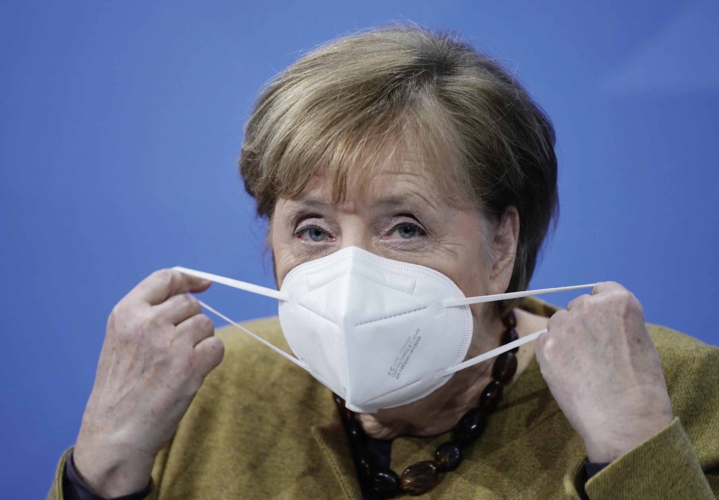 German Chancellor Angela Merkel removes a face mask as she arrives to address a press conference following videoconference talks with the prime ministers of the German states on the extension of the current partial blockade, at the Chancellery in Berlin on 5 January 2021.