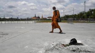 راهب يسير في ميدان سانام لوانغ أمام القصر الملكي في بانكوك في 21 ايلول/سبتمبر 2020 قرب بقعة خالية كان قادة حركة الاحتجاج المؤيدة للديموقراطية ركّبوا صفيحة معدنية فيها.