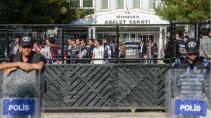 """Des officiers de police se tiennent devant le tribunal de Diyarbakir, alors que deux maires accusés de """"terrorisme"""" y sont conduits, le 30 octobre 2016."""