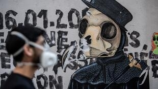 Artist Angel Crow stands before one of his works in a Paris street.
