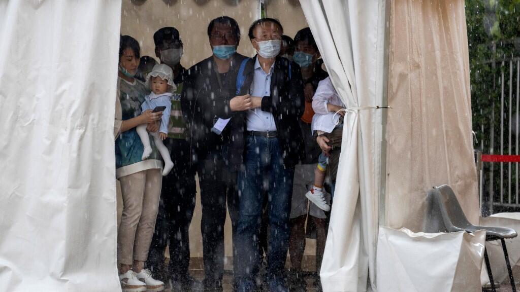 Ciudadanos portan tapabocas y se refugian bajo una carpa durante una tormenta en Beijing, 23 de mayo de 2020.