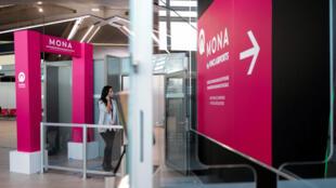 Une voyageuse se dirige vers le système expérimental de reconnaissance faciale Mona à l'aéroport de Lyon-Saint-Exupéry, le 5 octobre 2020