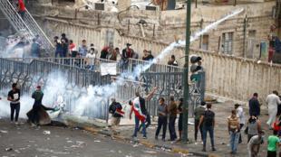 إلقاء قنبلة مسيلة للدموع على مجموعة من المتظاهرين  أثناء احتجاج على الفساد ونقص الوظائف وضعف الخدمات، في بغداد، العراق، 25 أكتوبر / تشرين الأول 2019.