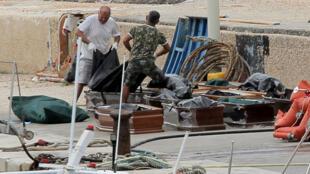 Les corps des victimes du naufrage sont placés dans des cercueils à Lampedusa, le 7 octobre 2019.