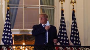 الرئيس الأميركي دونالد ترامب ينزع كمامته لدى عودته إلى البيت الأبيض من المستشفى في 10 ت1/أكتوبر 2020.