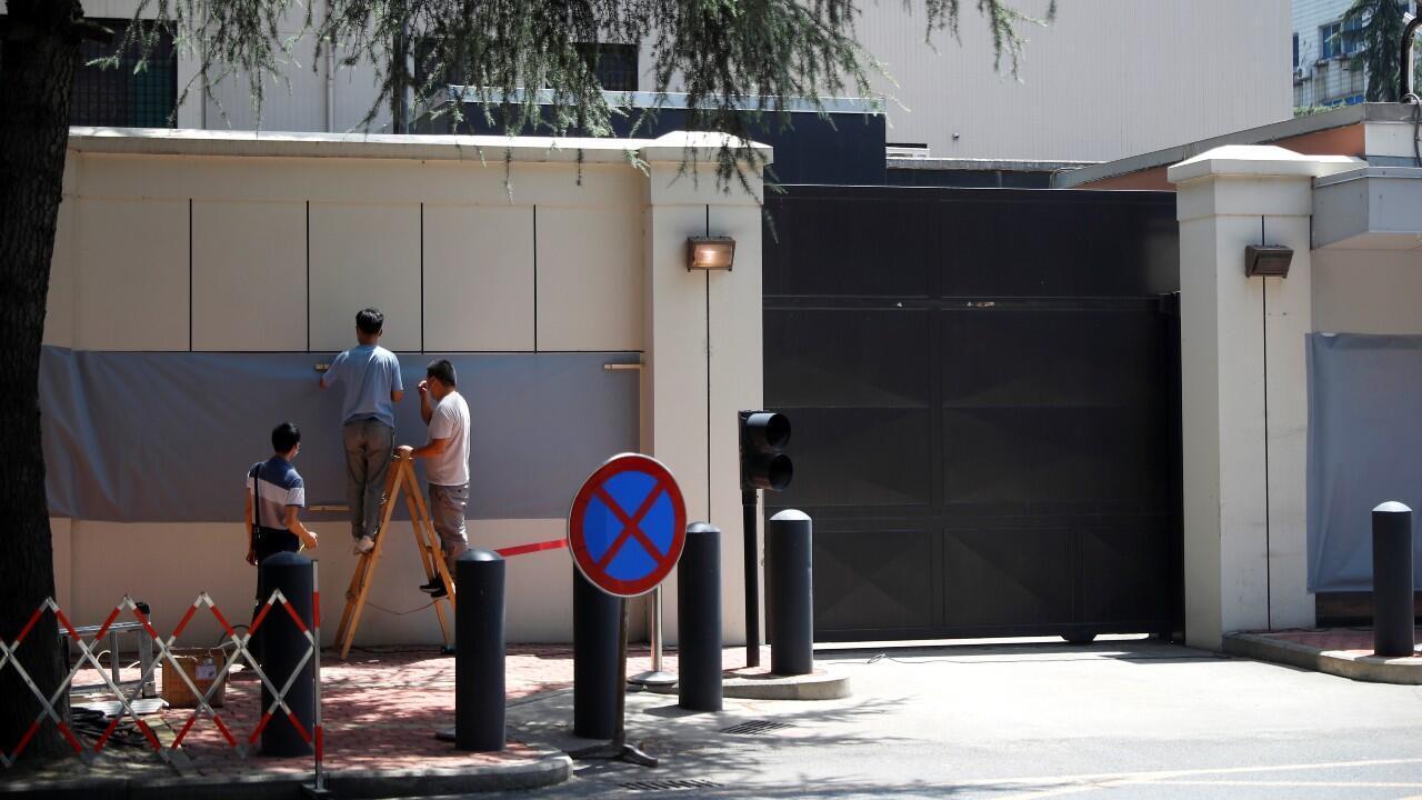 Momento en el que trabajadores colocan un soporte de madera para ocultar la señalización frente a lo que era el Consulado General de Estados Unidos en Chengdu.