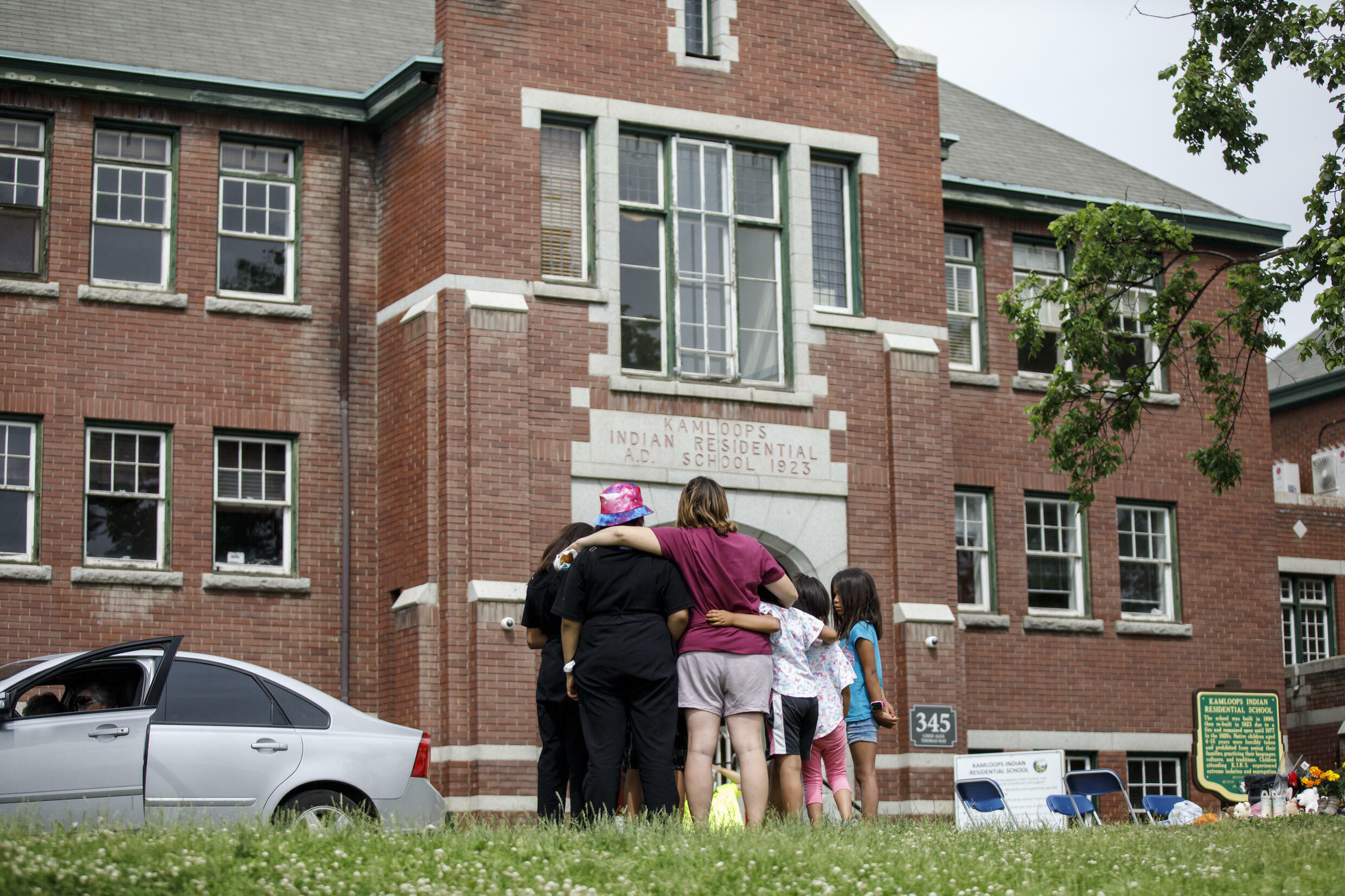 People look at the former Kamloops Indian Residential School where flowers and cards were left in June 2021 as part of a memorial to children whose remains were discovered buried near the facility
