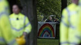 Una mujer y un niño se colocan detrás de una pancarta de un arocíris de esperaza mientras unos bomberos se preparan para aplaudir a los sanitarios que luchan contra el coronavirus el 30 de abril de 2020 en Hartley Wintney, al oeste de Londres
