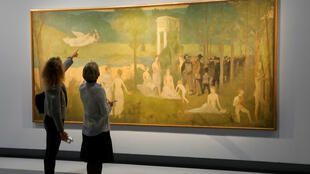 "Visitantes observan la pintura ""Parodie du 'Bois sacre"" de Pierre Puvis de Chavannes (1884) durante una visita de prensa de la exposición: Toulouse-Lautrec Resolument moderne, del artista francés Henri de Toulouse-Lautrec (1864-1901) en el Museo Grand Palais de París, el 4 de octubre de 2019."