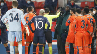 Referee Ovidiu Hategan is surrounded by players as the Champions League match between Paris Saint-Germain and Istanbul Basaksehir F.K. is interrupted at the Parc des Princes, in Paris, France, on December 8, 2020.