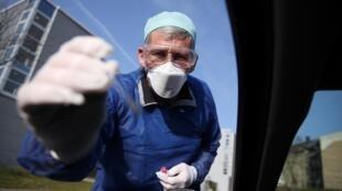 طبيب ألماني يجري تحليلا لفيروس كورونا لأحد المرضى في سيارته