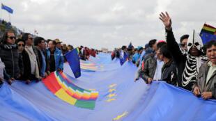 Varias personas sostienen una bandera por la reivindicación marítima en la Apacheta, cerca de El Alto, Bolivia, el 10 de marzo de 2018.