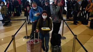 Trabajadores temporarios ucranianos aguardan en un aeropuerto de Kiev para abordar un vuelo a Finlandia