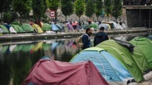 Des migrants rassemblent leurs affaires avant l'évacuation par la police, le long du Canal Saint-Martin, Quai de Valmy à Paris, le 4 juin 2018.