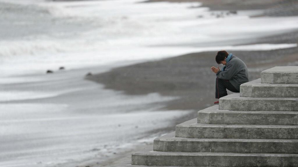 Una mujer frente al mar ora por las víctimas del tsunami y desastre nuclear de Fukushima, el 11 de marzo de 2019.