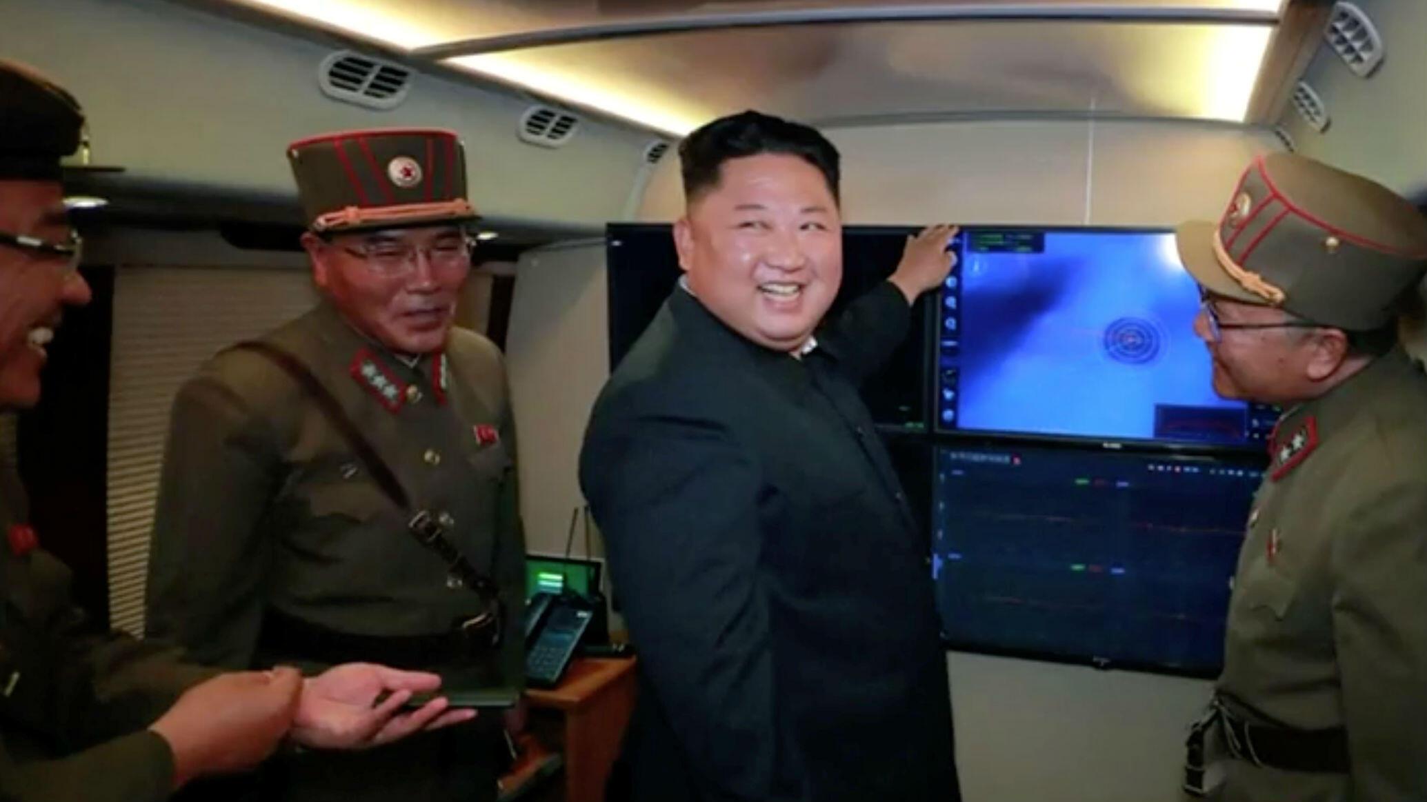 El líder norcoreano Kim Jong-un junto a los oficiales militares frente a una pantalla que se cree, muestra el lanzamiento de un proyectil en Corea del Norte, el 3 de agosto de 2019.