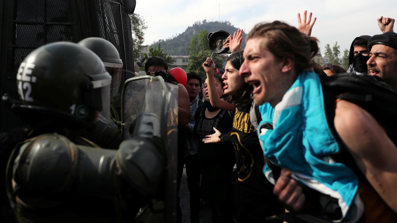 Los manifestantes gritan a los soldados durante una protesta contra el aumento de los precios al servicio del metro en Santiago, Chile, el 19 de octubre de 2019.
