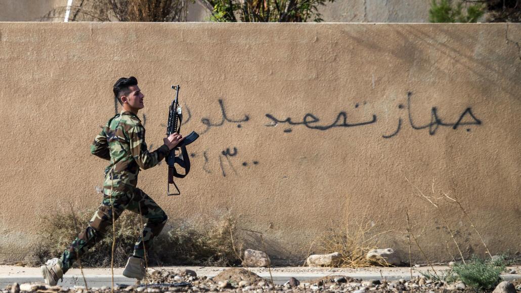 Un combattant kurde court se mettre à l'abri dans la ville de Bachika, au nord-est de Mossoul, le 8 novembre 2016.