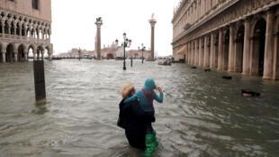 Una mujer sostiene a una niña mientras camina en una plaza inundada de San Marcos durante un período de marea estacional en Venecia, Italia, 29 de octubre de 2018