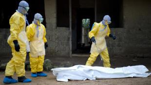 À à Momo Kanedou en Guinée, des médecins de MSF préparent le corps d'une victime d'Ebola avant de pouvoir le transporter, le 19 novembre 2014.